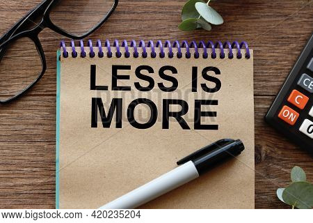 Less Is More. Text On Craft Paper On Wood Background Near Calculator.
