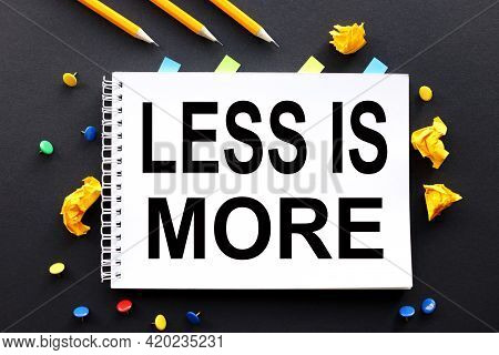 Less Is More. Text On White Paper On Black Background. And Multi-colored Buttons And Crumpled Paper