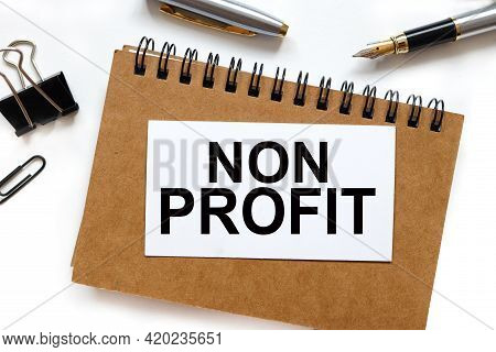 Non Profit. The Inscription On The Business Card On The Notebook. On White Background
