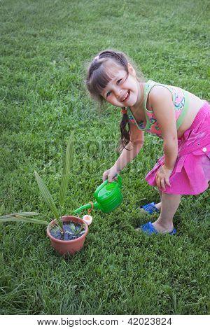 Little Girl Watering The Plants