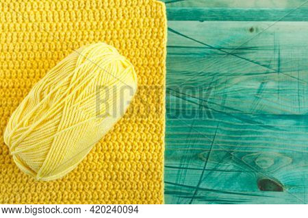 A Skein Of Yellow Yarn On A Background, Tied From Yellow Threads On A Green Wooden Background Of The