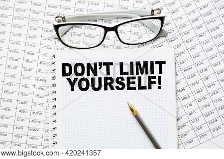 Notepad With Text Don't Limit Yourselfe On The Office Desk With Stationery. A Blank Notepad For Ente