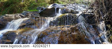 Panoramic Of Waterfall Of Water Falling Down The Rocks In The Enchanted Forest. Madrid Guadarrama.