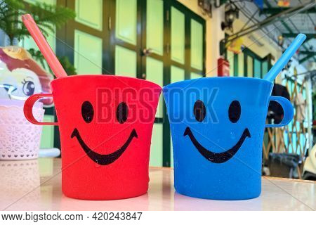 Bangkok, Thailand, April 16, 2017 : Red And Blue Water Glasses In Restaurant Have A Happy Face And S