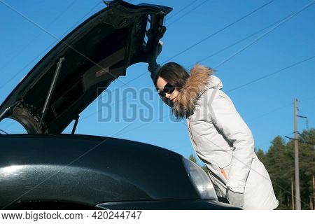 Young Woman In A Jacket Opens The Hood Of Her Car From The Front. Puzzled Woman Near Broken Car, Loo
