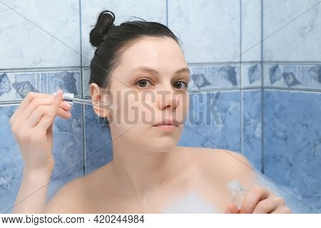 Young Woman Is Applying Hyaluronic Acid On Face Skin Taking A Bath With Foam. Rejuvenating And Moist