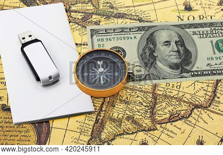 Classic Navigation Compass On American Dollars Flash Drive On White Paper On Old Vintage World Map A