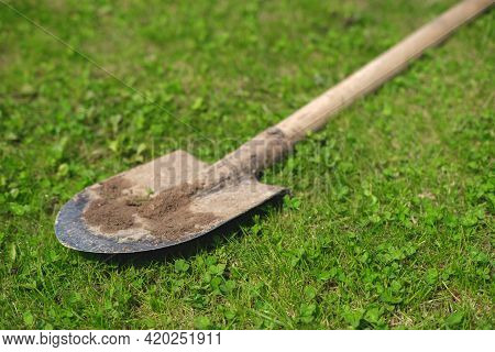 A Dirty Shovel Casts A Shadow On The Grass.