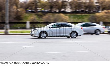 Fast Moving Toyota Camry On The City Road. Rental Silver Sedan Car Is Driving Down The Street. Used