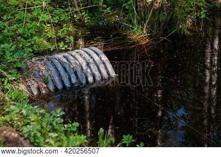 Large Plastic Gutter Pipe In A Forest River Ditch.