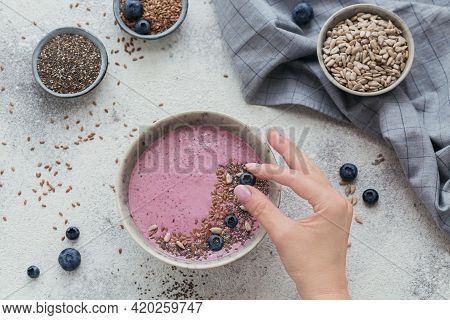 Woman's Hands Holding Blueberry For Decorating Pink Yogurt Smoothie Bowl Made With Fresh Blueberry A
