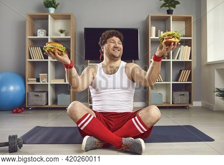 Excited Millennial Man With Chubby Body Holding Fast Food Burger In Two Hands
