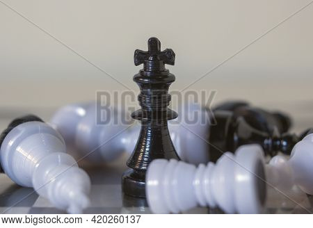 3d Icon Object Of A Black Standing King Chess Piece Surrounded By Fallen Pawns. Board Games. Chess P