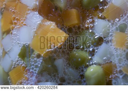 Extreme Closeup Macro Shot Of Chopped Vegetables In A Transparent Jar With Carrot, Potato And Green