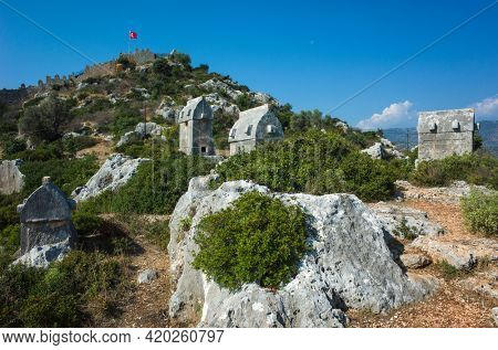 Lycian rock tombs and Simena fortress with Turkish flag on hill in Simena (Kalekoy), Turkey. Rock sarcophagus at ancient Lycian necropolis