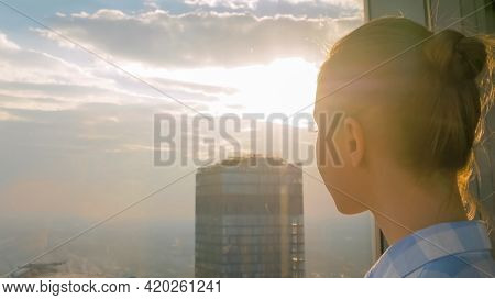 Portrait Of Woman Looking At Cityscape Through Window Of Skyscraper - Close Up. Summer Time, Sunset,