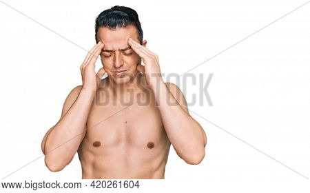 Handsome young man wearing swimwear shirtless with hand on head, headache because stress. suffering migraine.