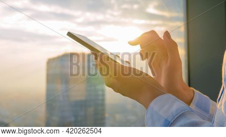 Close Up Of Woman Using Smartphone Device Against Sunset Cityscape View Through Window Of Skyscraper