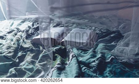 Image Of A Open Book On A Bed In The Morning Light. Shot Through A White Mosquito Net