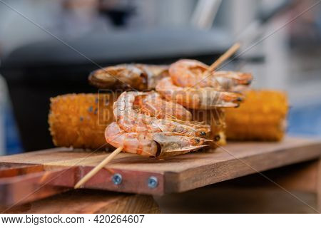 Grilled Shrimp, Prawn Skewer And Corn Cobs On Wooden Cutting Board At Summer Outdoor Food Market: Cl