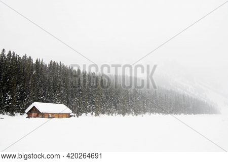 Beautiful Winter Landscape With Snow. A Wooden House Close To A Forest During A Heavy Snow Storm. Ba
