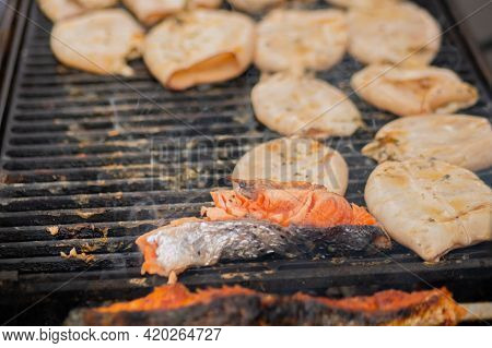 Process Of Cooking Squids And Salmon Steaks On Grill At Summer Local Food Market - Close Up. Outdoor