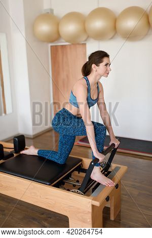 An Athletic Woman Does An Exercise On A Reformer In The Gym.
