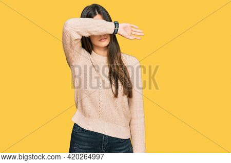 Young brunette woman wearing casual winter sweater covering eyes with arm, looking serious and sad. sightless, hiding and rejection concept