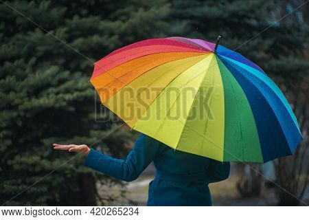 A Girl In A Green Coat Hides Under An Umbrella Of Rainbow Colors From The Rain. The Girl Removed Her