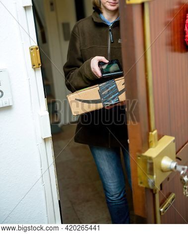 Paris, France - Jan 27, 2016: Delivery Female Courier Employee Scanning With The Barcode Scanner Dev