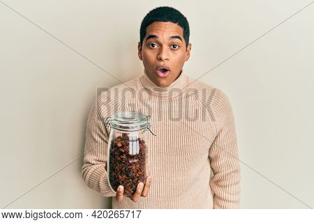 Young handsome hispanic man holding jar full of raisins scared and amazed with open mouth for surprise, disbelief face
