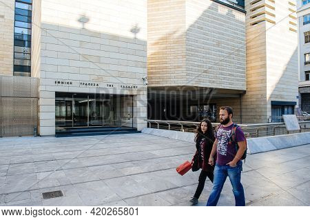 Athens, Greece - Mar 29, 2016: Young Greek Couple Walking In Front Of Modern Building Of National Ba