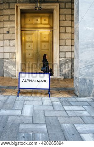Athens, Greece - Mar 29, 2016: Elegant Greek Woman Walking In Front Of The Tall Gate Of Alpha Bank W