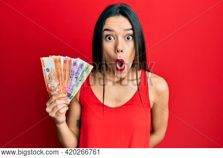 Young hispanic girl holding philippine peso banknotes scared and amazed with open mouth for surprise, disbelief face