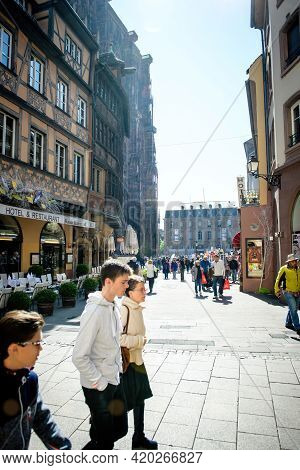 Strasbourg, France - Apr 21, 2017: Group Of Young Tourists Walking In Front Of Notre-dame Cathedral
