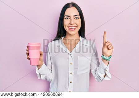Beautiful woman with blue eyes drinking a take away cup of coffee smiling with an idea or question pointing finger with happy face, number one