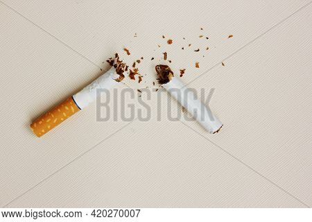 A Broken Cigarette On A White Background. Tobacco Sheet Is Racially Pand. View From Above. The Conce