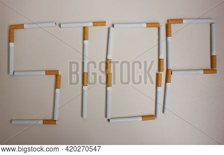 The Word Stop Is Drunk With Cigarettes On A White Background. View From Above. The Concept Of World