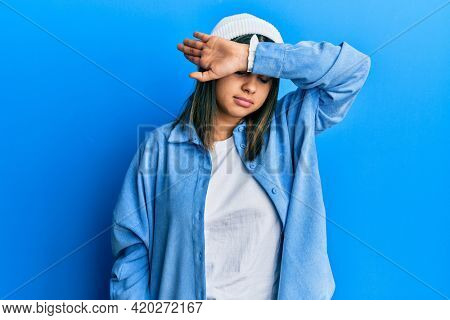 Young latin woman wearing cute wool cap covering eyes with arm, looking serious and sad. sightless, hiding and rejection concept