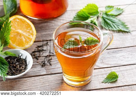 Healing Tea With Nettle. Tea In A Glass Cup On A Wooden Table. Folk Remedy. The Source Of Vitamins.
