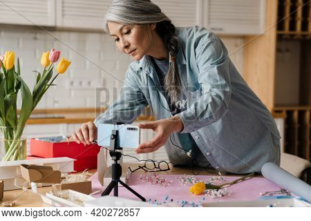 Mature grey woman installing her cellphone on tripod for selfie footage at home