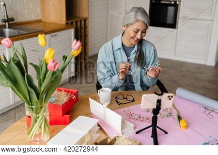 Smiling grey woman showing costume jewelry while taking selfie footage on cellphone at home