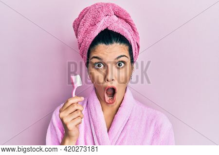 Young hispanic woman wearing shower bathrobe holding toothbrush scared and amazed with open mouth for surprise, disbelief face