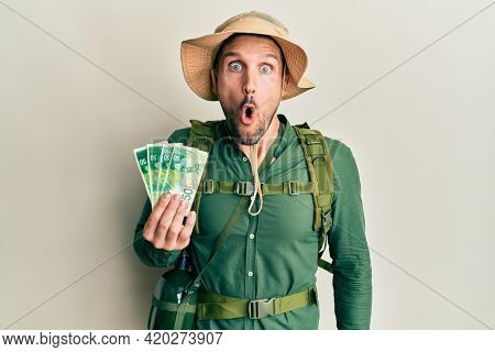 Handsome man with beard wearing explorer hat holding 50 shekels scared and amazed with open mouth for surprise, disbelief face