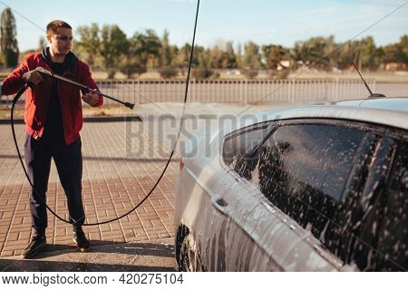 A Man Washes A Car With A Pistol At A Self-service Car Wash