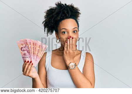 Young african american girl holding thai baht banknotes covering mouth with hand, shocked and afraid for mistake. surprised expression