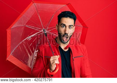 Young hispanic man holding umbrella scared and amazed with open mouth for surprise, disbelief face