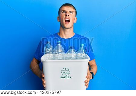 Young caucasian man holding recycling wastebasket with plastic bottles angry and mad screaming frustrated and furious, shouting with anger looking up.