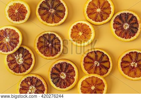 Group Of Fresh Organic Sicilian Blood Oranges Sliced Over Yellow Background. Flat Lay, Space