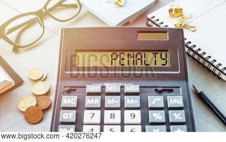 Word Penalty Written On Calculator On Office Table.